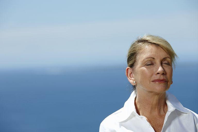 woman with eyes closed looking at peace with a blue background