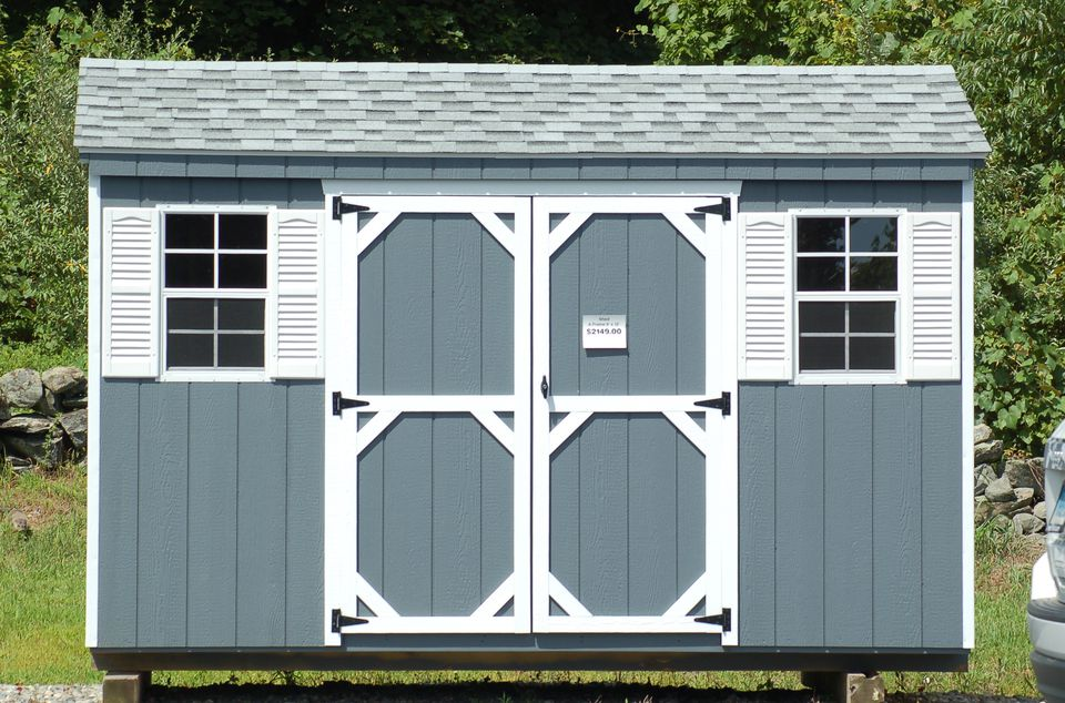 Image: gray shed with white trim.