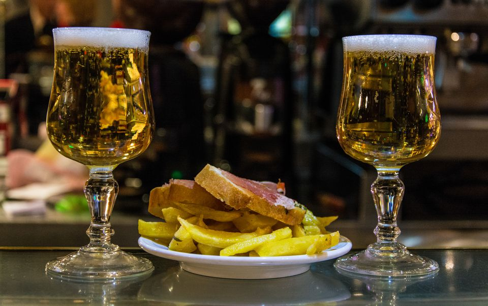Close-Up Of Beer Glasses With French Fries And Bread On Table