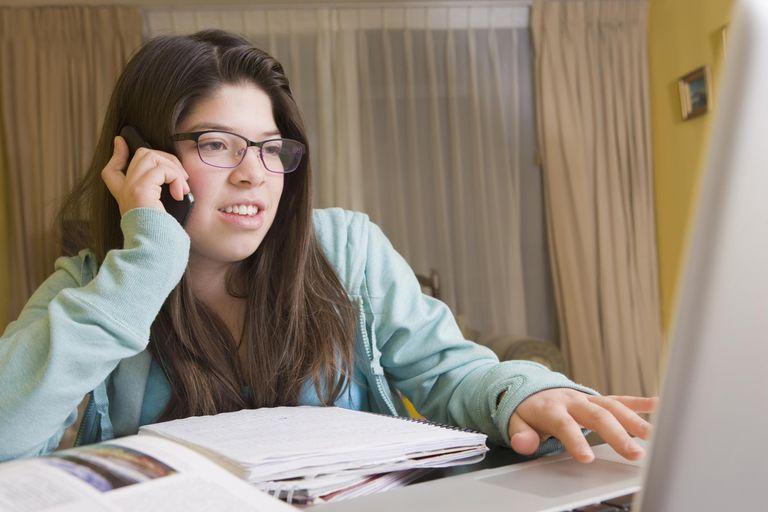 Hispanic girl talking on cell phone at laptop