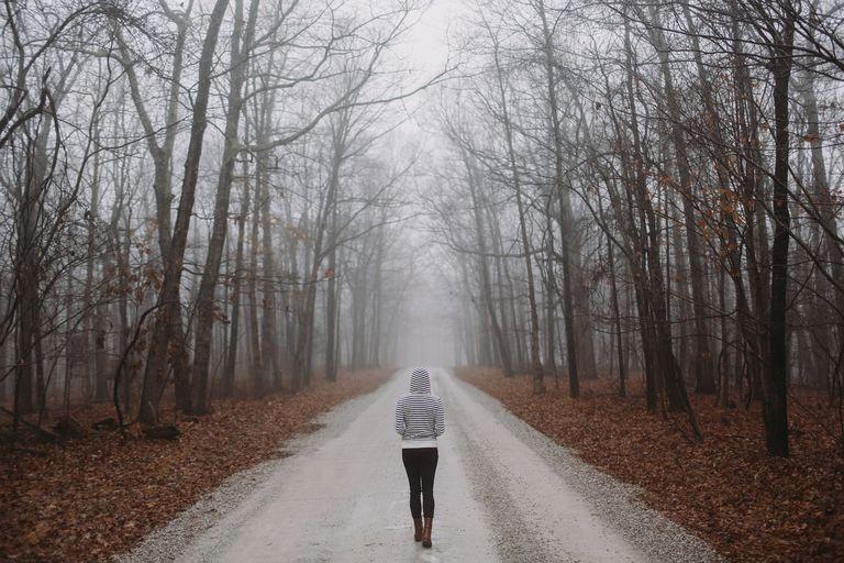 Girl Walking Alone on Gravel Road in Autumn