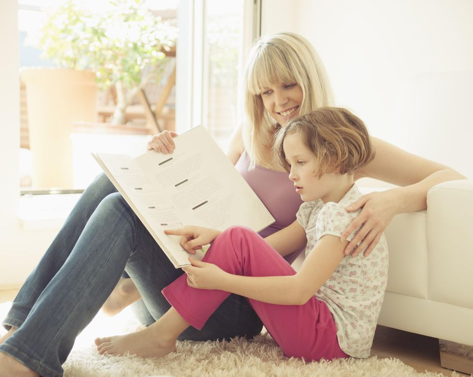 Young girl reading with mother