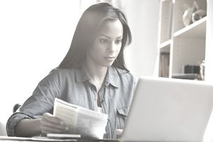 Mixed race woman paying bills on laptop