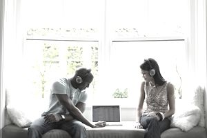 Young man and teenage girl (15-17) listening to music on laptop