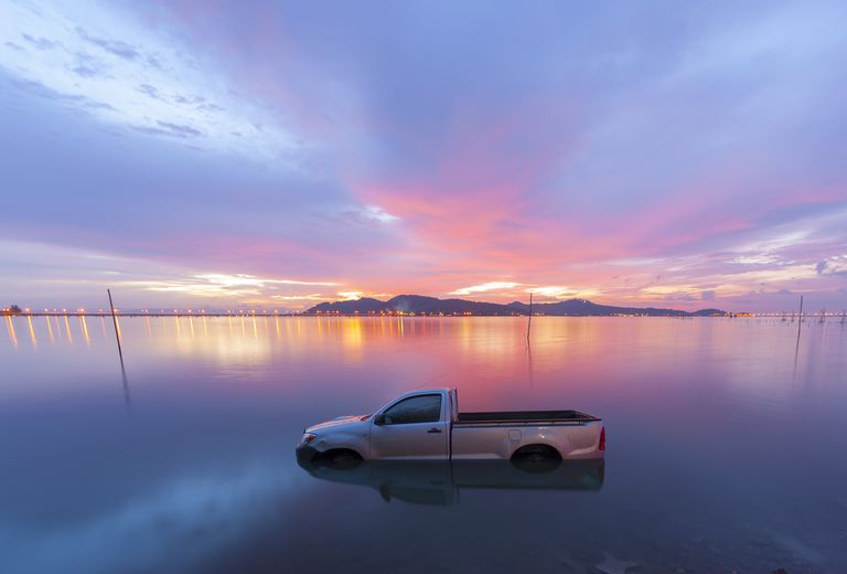 Automobile sinking in water Sunset
