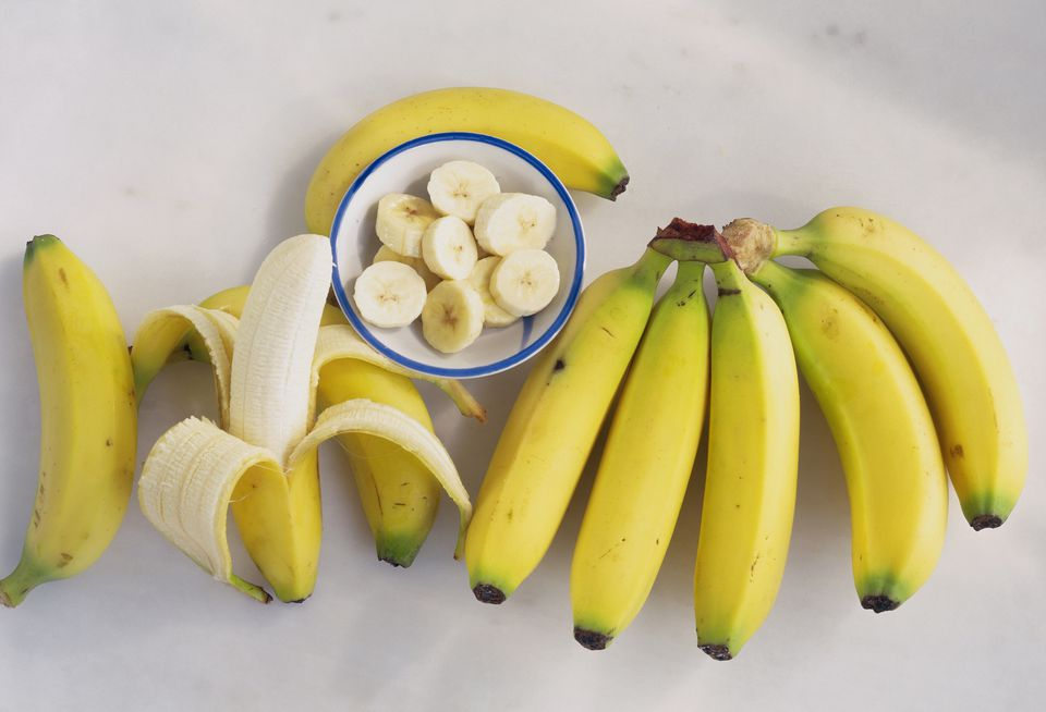 Bunch of bananas with one peeled, one sliced