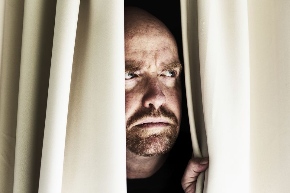 Man peeping through curtains