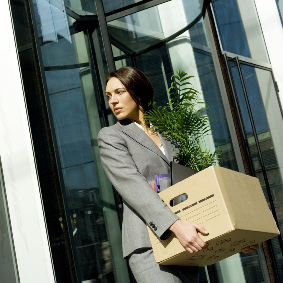 A woman leaves her office with a box of her things