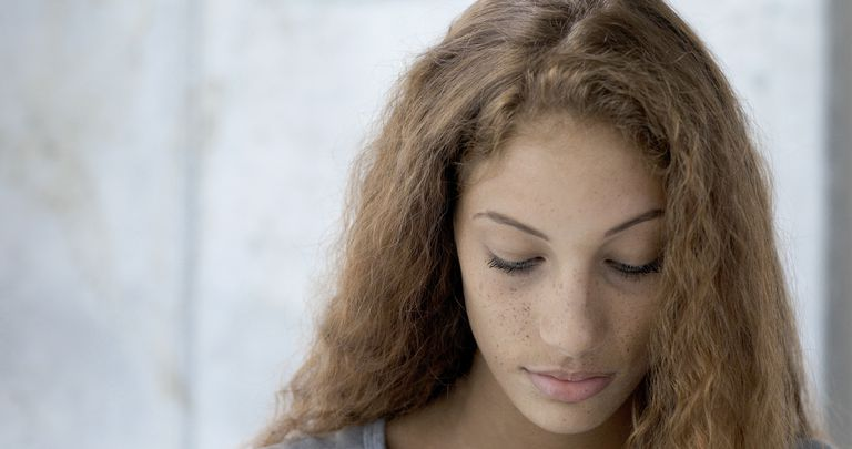 Headshot of female, mixed race teenager looking down.