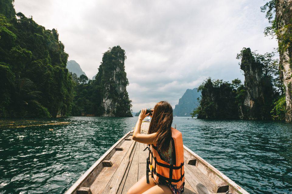 Female tourist exploring lush Jungle lake surrounded by limestone cliffs, Khao Sok National Park, Thailand