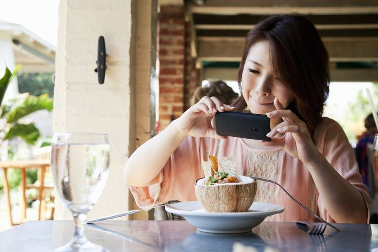 Woman taking photo of food on her phone