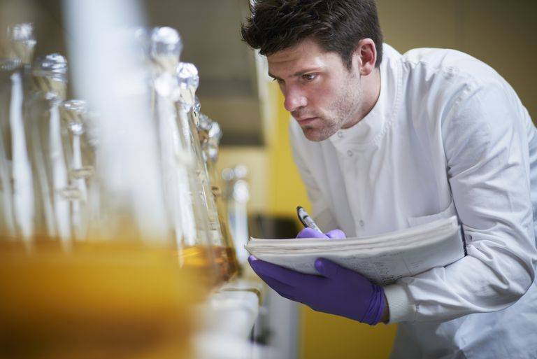 Male science student looking at flasks and making notes