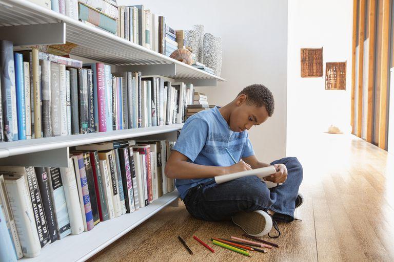 Boy (10-11) drawing at home