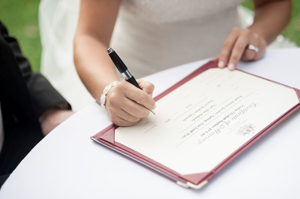 Bride signing marriage certificate