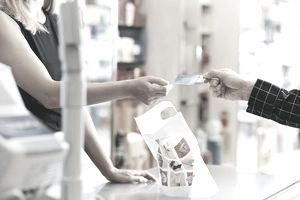 Shop Assistant Takes Payment By Credit Card on Perfume Counter