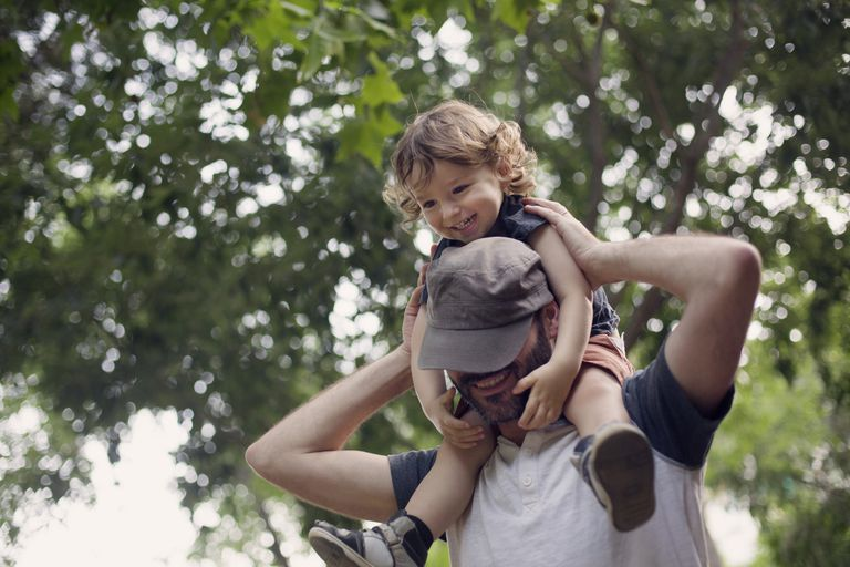 Dad carries boy in shoulders both looking happy
