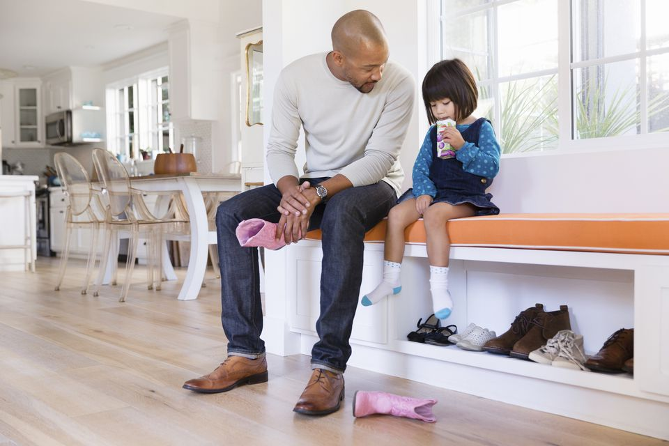 Father holding pink cowboy boots next to toddler daughter drinking juice box on window seat