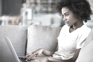 Shot of a young woman using a laptop while relaxing at home