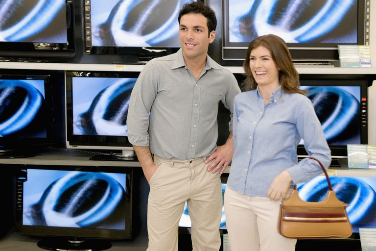 Couple smiling in front of televisions in a supermarket