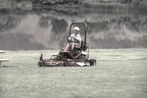 woman riding lawnmower in park