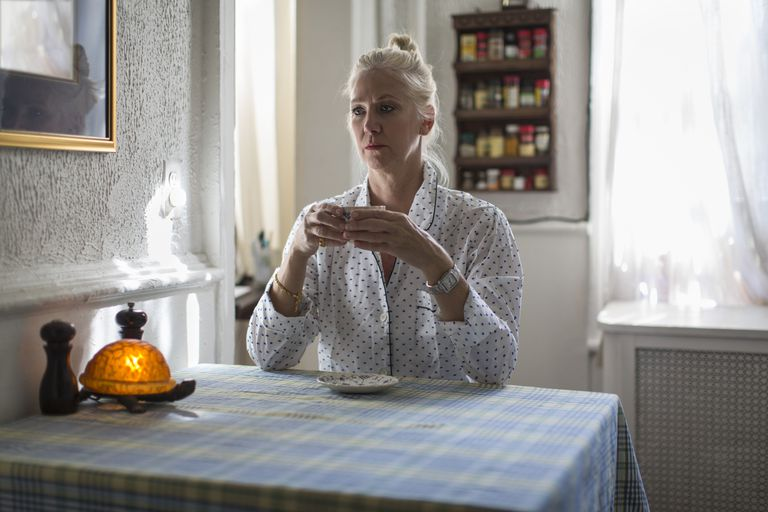 Menopausal woman sitting at table with tea cup looking depressed