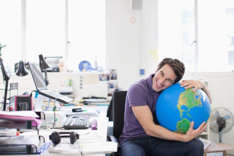 Smiling businessman hugging globe at desk in office