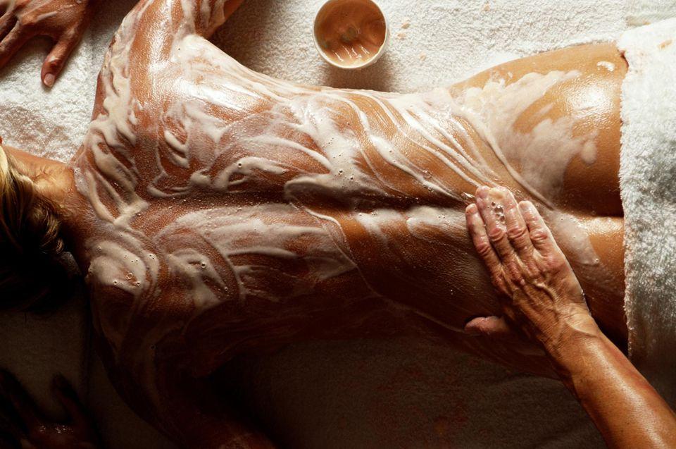 Woman receiving body scrub, overhead view