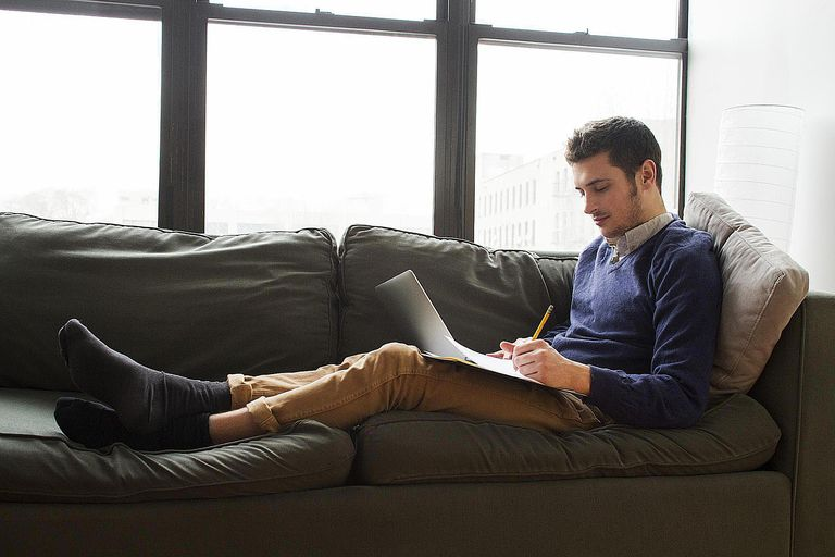 Young Man Relaxing on Couch and Doing Homework