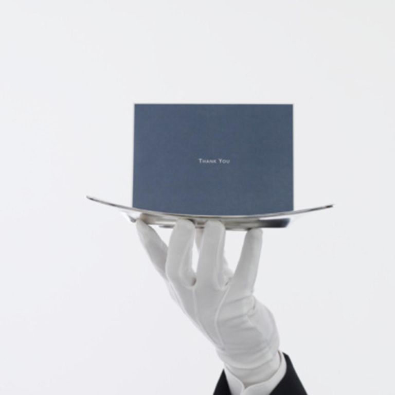 Waiter with greeting card on serving tray, close up of hand