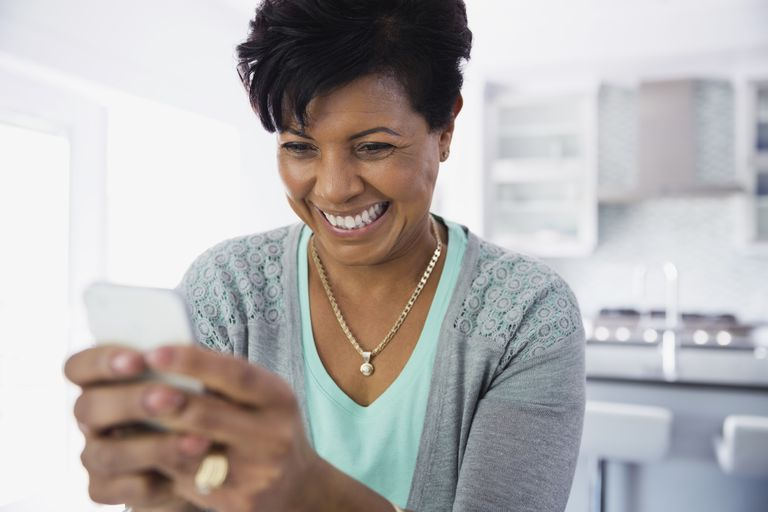 Woman text messaging on smartphone at home