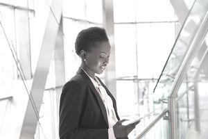 Corporate businesswoman using digital tablet in modern office lobby