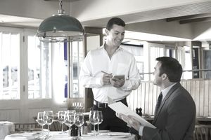 Waiter and man in restaurant