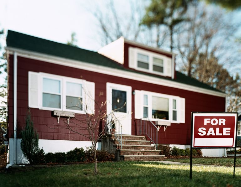 'For sale' sign on lawn in front of house