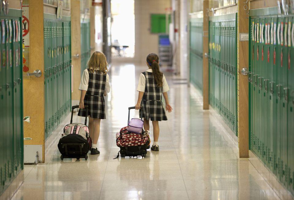 Second grade girls roll backpacks in school