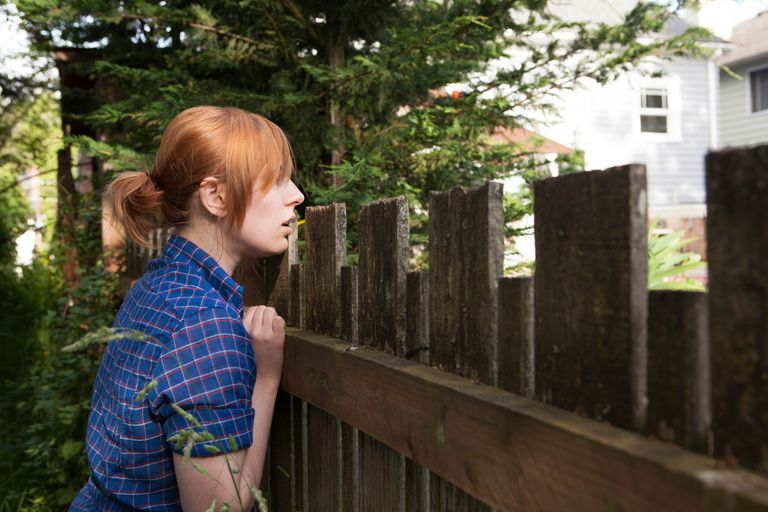 Woman peering over fence at neighbor's yard.
