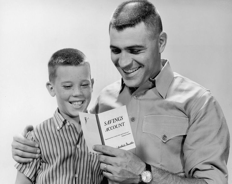 Father and son reading their savings account statement.
