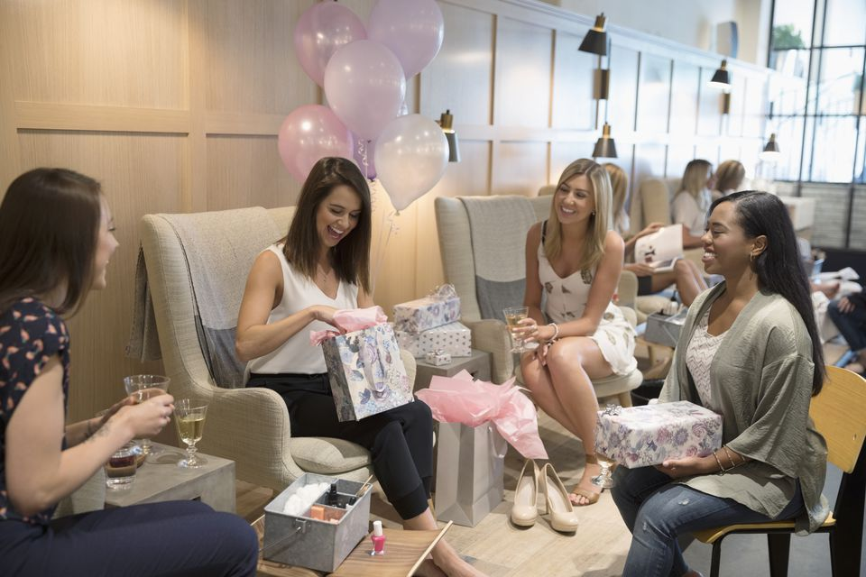 Bride-to-be and bridesmaid friends opening gifts at bridal shower in nail salon