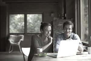 A man and a woman looking at a laptop