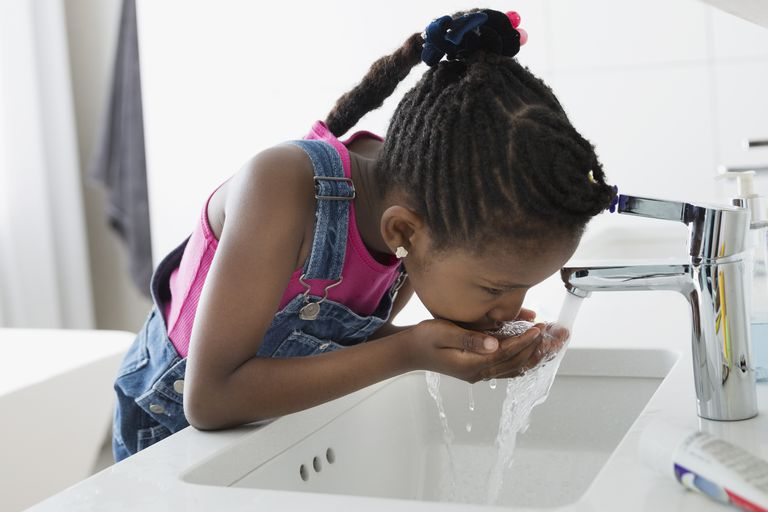 Girl drinking water from faucet at bathroom sink