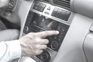 A picture of a man in the car changing his radio station