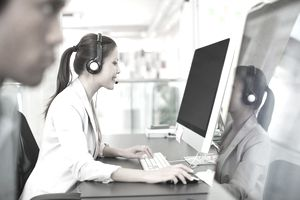 Portrait of confident businesswoman with headset at computer in office