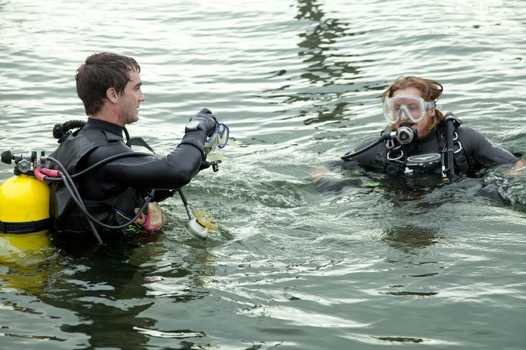 Two scuba divers, age 32 and 36, above water ready to go under