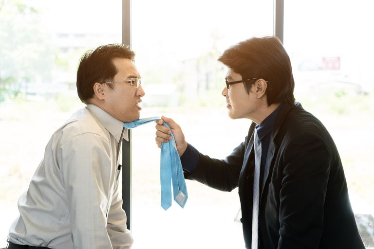 Asian businessman manager shouting to a stressed employee in office on meeting. Fighting businessmen tearing each other at their ties.
