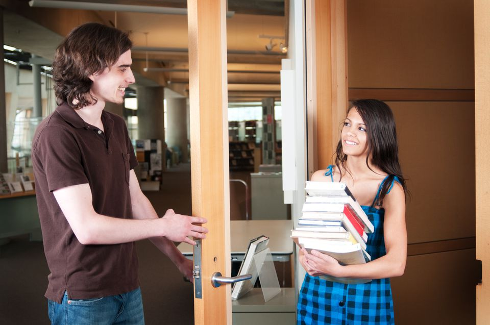 Man holding the door for woman with books