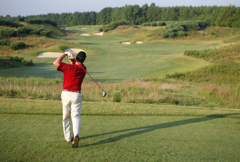 golfer tees off on a hole