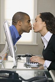 Picture of a woman kissing a man through her computer monitor during online infidelity