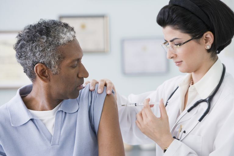 Doctor giving vaccination to man