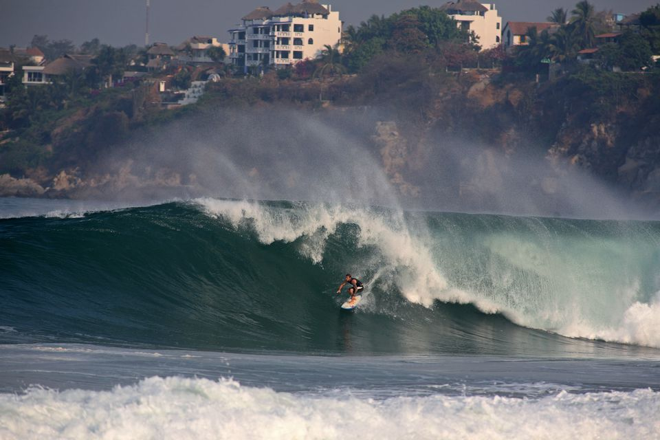 Surfer on large wave at Zicatela Beach, famous surfing beach also known as Mexican Pipeline.