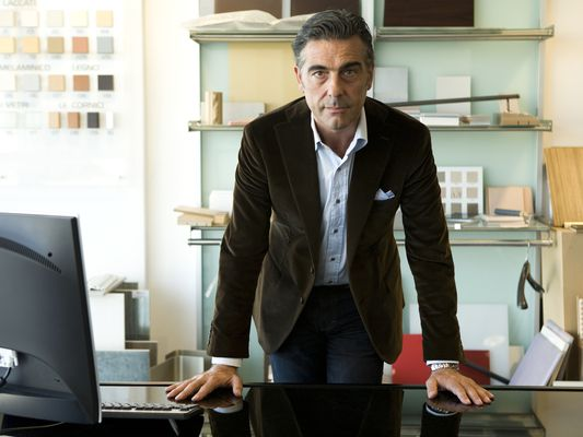 a business man leaning on a desk looking stoic