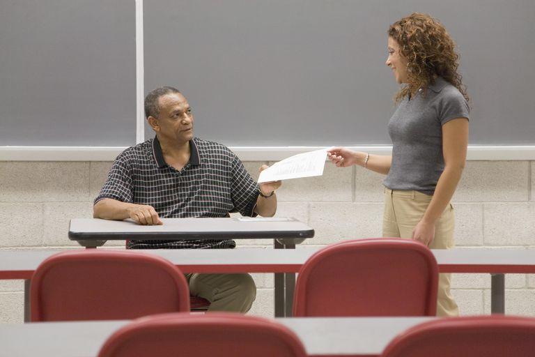 College student handing professor paperwork